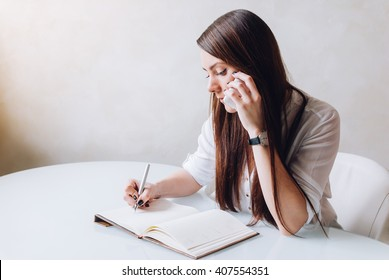 A young beautiful receptionist and personal assistant is very serious. She is making a phone call and taking notices as a business woman