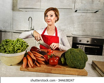 young beautiful red hair woman in red apron at home kitchen preparing vegetable salad with lettuce, carrots and slicing tomato smiling happy in healthy veggie eating and diet concept