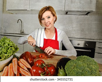young beautiful red hair woman in red apron at home kitchen preparing vegetable salad with lettuce slicing tomato smiling happy in healthy veggie eating and diet concept grunge dirty edit