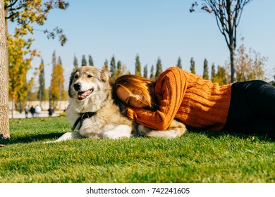 young beautiful red-haired girl in a trendy orange sweater walking with her dog in the park