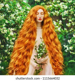 Young beautiful red-haired girl with very long curly hair with freckles on her face. Fabulous model with freckles against the background of a blooming spring garden