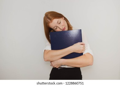 young beautiful red-haired woman hugging a folder and sleeping on a folder against a white background, businesswoman