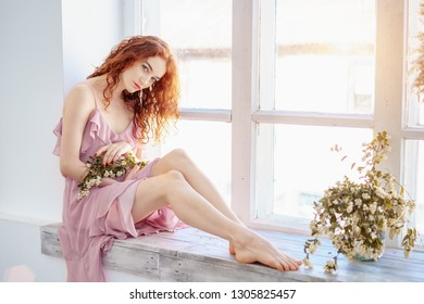 young beautiful red-haired woman sitting near the window with a flower, spring mood