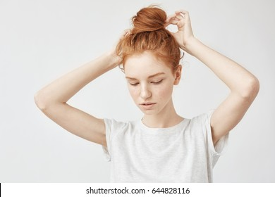 Young beautiful redhead girl correcting hair bun.