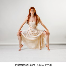 Young and beautiful redhead girl dancer posing in studio. Copy space