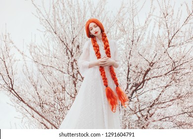 Young beautiful redhead girl with plait on spring flower background. Woman with pale skin and long red plait on nature. Blooming spring cherry tree in park. Kawaii girl. Blooming sakura in nature