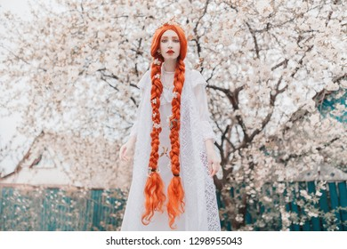 Young beautiful redhead girl with plait on spring blossom plant background. Redhead woman in white dress in garden. Blooming spring cherry plant in park. Japan girl. Blossom sakura in garden