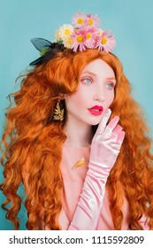 Young beautiful redhead girl with very long hair and pink gloves in studio on a blue background. Fabulous renaissance redhead model with flowers in red  curly hair