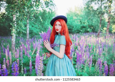 Young beautiful redhead girl with very long hair on lupine background. Fabulous renaissance woman in mint dress against the backdrop of a beautiful flowers. Spring blue lupine grow on a meadow
