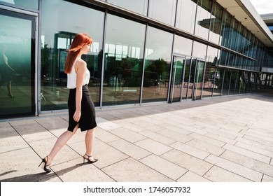 Young beautiful redhead self-confident business woman walking outside wearing formal black and white office clothes and high heels near a modern glass office building on summer sunny day