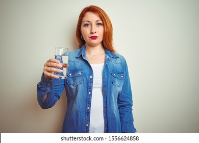 Young beautiful redhead woman drinking glass of water over white isolated background with a confident expression on smart face thinking serious