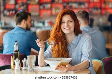 Young beautiful redhead woman eating vegetarian salad.