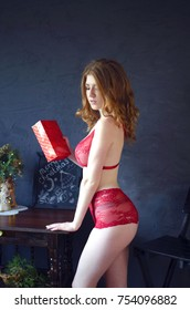 94f85609382 Young beautiful redhead woman with gift box on her hands. Christmas happy  celebration