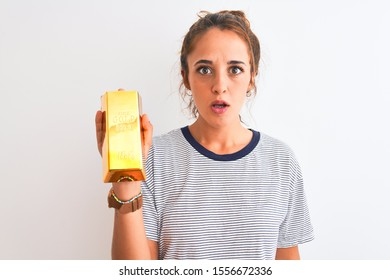 Young beautiful redhead woman holding gold ingot over isolated background scared in shock with a surprise face, afraid and excited with fear expression
