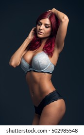 Young Beautiful Redhead Woman Looking Away Posing In Blue Lingerie With Shiny Elegant Red Hair.