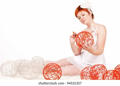 Young beautiful redhead woman paints the white balls in orange
