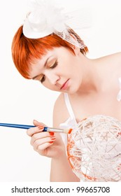 Young beautiful redhead woman paints the white ball in orange