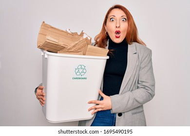 Young beautiful redhead woman recycling holding trash can with cardboard to recycle scared in shock with a surprise face, afraid and excited with fear expression
