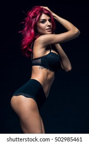 Young Beautiful Redhead Woman Seductively Looking At Camera Standing Posing In Black Lingerie With Shiny Elegant Red Hair.