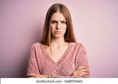 Young beautiful redhead woman wearing casual sweater over isolated pink background skeptic and nervous, disapproving expression on face with crossed arms. Negative person.