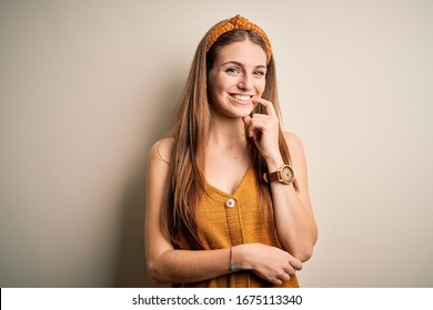 Young beautiful redhead woman wearing casual t-shirt and diadem over yellow background looking confident at the camera with smile with crossed arms and hand raised on chin. Thinking positive.