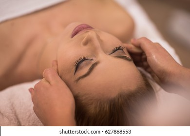 Young beautiful relaxed woman receiving a head massage in a spa centre