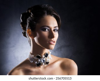 Young, beautiful and rich woman in jewels of platinum and stones over luxury background