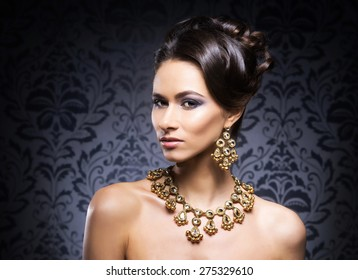 Young, beautiful and rich woman in jewels of gold and stones over luxury background