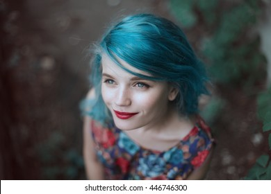 Young, beautiful and romantic woman with blue hair and red lips is smiling and looking to the sky