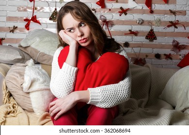 Young beautiful sad brunette girl in a white knitted sweater with red heart shaped decor sitting alone in bedroom on Valentine's Day