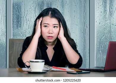 young beautiful sad and depressed Asian Korean business woman working exhausted and frustrated at office computer desk with rain on the window suffering depression and anxiety problem