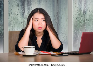 young beautiful sad and depressed Asian Chinese business woman working exhausted and frustrated at office computer desk with rain on the window suffering depression and anxiety problem