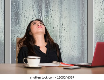 young beautiful sad and depressed Asian Chinese businesswoman working exhausted and frustrated at office computer desk with rain on the window suffering depression and anxiety problem