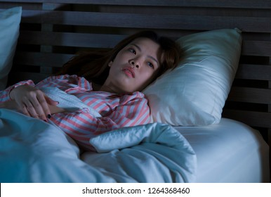 young beautiful sad and depressed Asian Chinese girl lying on bed late night awake looking thoughtful suffering insomnia sleeping disorder feeling tired and worried in woman depression concept