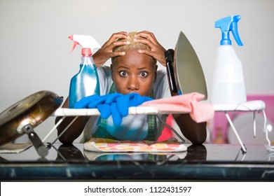 young beautiful sad and desperate black African American woman feeling stressed working frustrated at home kitchen with domestic labour stress in tired and overworked housewife concept