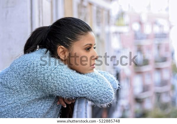 молодая красивая грустная и отчаянная испаноязычная женщина, страдающая депрессией, глядя вдумчивый и разочарованный в квартире балкон глядя в депрессию на улице
