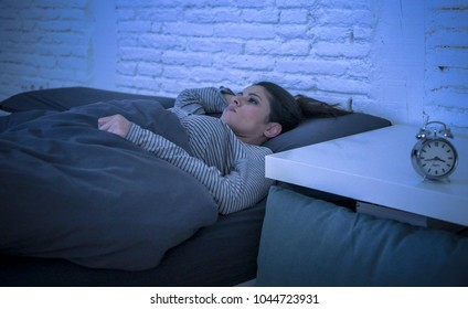 young beautiful sad and worried latin woman suffering insomnia and sleeping disorder problem unable to sleep late at night lying on bed awake feeling stressed and frustrated