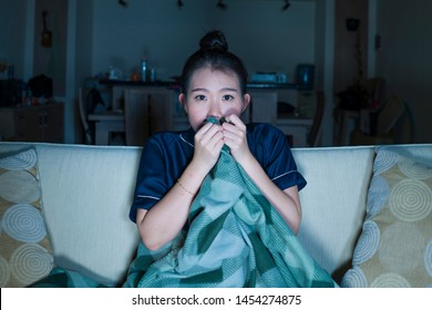 young beautiful scared and frightened Asian Korean woman watching horror scary movie or thriller eating popcorn in fear face expression eating popcorn sitting at living room couch in the dark