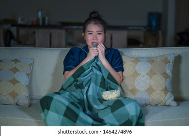 young beautiful scared and frightened Asian Japanese woman watching horror scary movie or thriller eating popcorn in fear face expression eating popcorn sitting at living room couch in the dark
