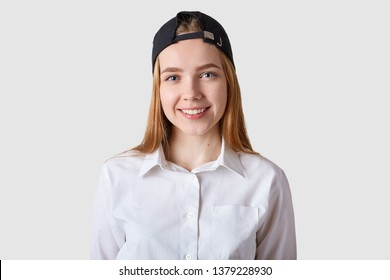 Young beautiful schoolgirl posing in white blouse. Eighteen years old teenage girl looking at camera over bright studio background, being in good mood, has pleasanr expression. Youngster concept.