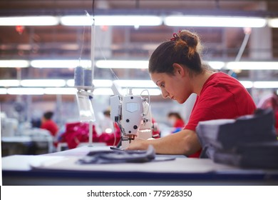 Young beautiful seamstress is working of cloth factory