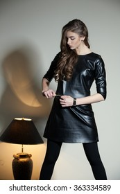 Young and beautiful seductive woman in a black vinyl/leather dress,black tights and shoes