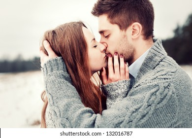 Young beautiful sensual couple outdoor portraits. Boy and girl having fun in cold weather.