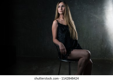 young beautiful sensual girl in a light dark dress with dark hair, sitting on the chair, in a room with gray walls, in which the rain falls. Aqua Studio