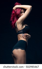 Young Beautiful Sensual Redhead Woman Looking At Camera Standing Posing In Black Lingerie With Shiny Elegant Red Hair.