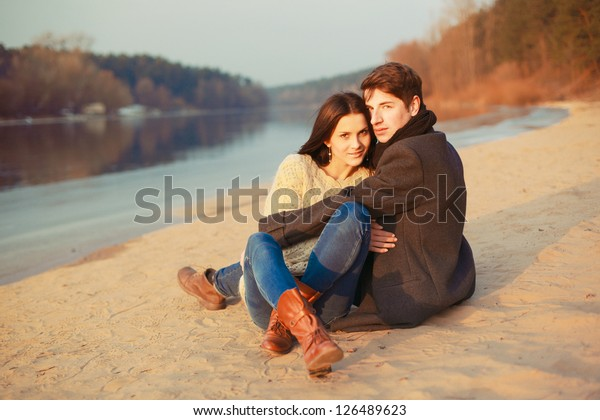 Young beautiful sensual stylish couple in love sitting on sand near the river