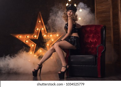 Young beautiful sexy girl with curls in a fetish dress latex and leather on an antique chair and on the background of a star with lamps