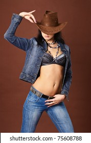 Young beautiful sexy girl in jeans and a cowboy hat on brown background