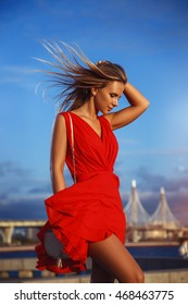 Young beautiful sexy girl in red dress walks along the promenade on the background of the bridges at sunset