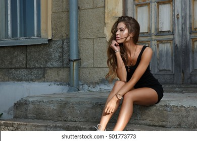 Young beautiful and sexy girl with slim sun tanned attractive body dressed in a slinky black singlet is posing outdoor sitting on the steps and looking into the distance in the summer city.